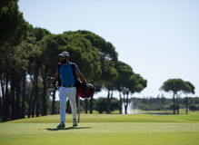 Golf player walking and carrying bag Royalty Free Stock Photos