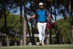 Golf player walking and carrying bag Royalty Free Stock Image