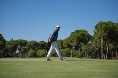 Golf player walking and carrying bag Royalty Free Stock Photo