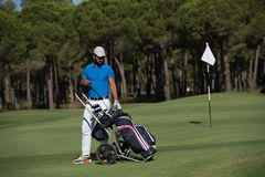 Golf player walking with wheel bag Stock Images