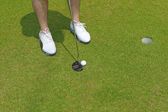Golf player with white shoes holding a club with golf ball near Stock Image