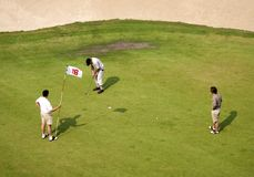 Golf players. Three golf players finishing the game royalty free stock image