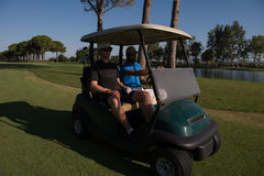 Golf players driving cart at course Royalty Free Stock Images