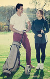 Golf players at golf course. Positive male and female golfers are ready for tour of game at golf course Stock Images