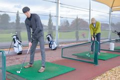 Golf players hitting shot with club on course stock images