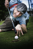 Golf Or Pool. Laughing With A Crazy Grin A Mixed Up Sports Man Plays Pool Using His Golf Club As A Snooker Que Aiming For The Greens Hole Stock Photo