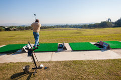 Golf Practice Range Player. Mature male hitting some balls at the golf practice range with at Mount Edgecombe golf courses one and two outside Durban South Royalty Free Stock Photos