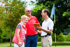 Golf pro with senior woman and man analyzing results Royalty Free Stock Images