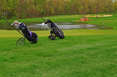 Golf Push Carts. Two Portable Golf Push Carts with golf bags on Green Turf, concept for leisure, travel, fun sports, or exercises stock photography