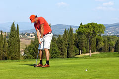 Golf put. Golfer putting a ball on the green of a golf course Royalty Free Stock Image