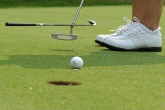 Golf putt. Golfer putting the ball into the hole on the putting green Stock Photography