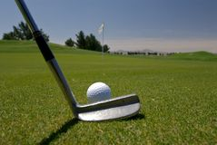 Golf Putt. Long distance to a flag with putter in foreground Royalty Free Stock Image
