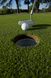 Golf Putt. A short put in the game of golf with a ball and a putter Royalty Free Stock Photography