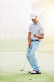 Golf putt green. Golf man putting on green and aiming to sink golf putt shot on course Stock Image