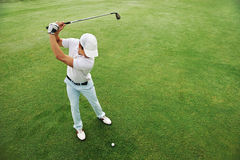 Golf putt green. Golf man putting on green and aiming to sink golf putt shot on course Royalty Free Stock Photos