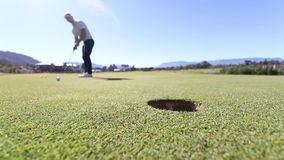 Golf putt. Ground level Footage of a golf ball being putted into a hole with the focus on the hole and the golfer out of focus stock footage