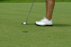 Golf putt2. Golfer putting the ball into the hole on the putting green stock images