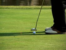 Golf Putter. A man lines up his putt and takes the shot Royalty Free Stock Photography