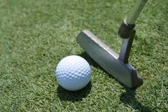 Golf Putter, Ball and Green. Closeup of golf putter and ball against blurred background of green grass. Horizontal format Royalty Free Stock Photo