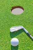Golf putter ball near the hole in the vertical format. Royalty Free Stock Photography