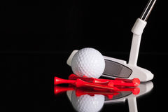 Golf putter and gold equipments on the black glass desk Stock Image