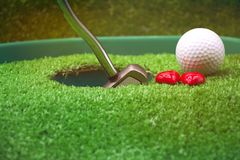 Golf and  with putter on green background. Golf and putter are on green grass Royalty Free Stock Images