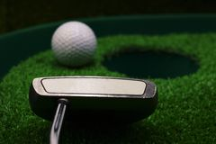 Golf and with putter on green background. Golf and putter are on green grass Royalty Free Stock Photos