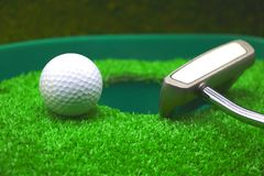Golf and with putter on green background. Golf and putter are on green grass Royalty Free Stock Photography