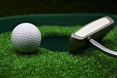 Golf and  with putter on green background. Golf and putter are on green grass Stock Photo