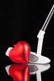 Golf putter and love symbol. Golf putter and red heart on the black glass desk Stock Photo