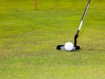 Golf: putterklubba med vit golfboll Arkivbilder