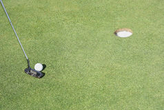 Golf putting. Putter club ball and hole putting detail one the golf course Royalty Free Stock Images