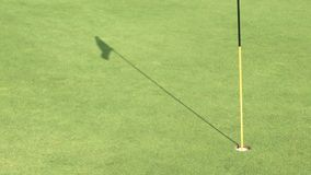 Golf putting green. With flag stick and shadow of flag stock footage