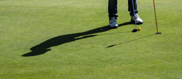 Golf putting. Unrecognisable man putting on a nice green golf during a sunny day with his shadow stock image