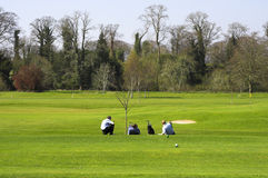 Golf and Relax. Golf partners relaxing on the golf field Royalty Free Stock Photography