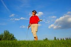Golf, riendo al golfista de la mujer, con un palillo y una bola en su mano Imagen de archivo libre de regalías