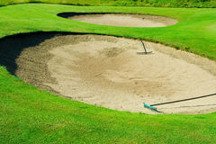 Golf sand traps. A pair of sand traps on a green slope, rakes on the sand Royalty Free Stock Images