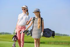 Golf school. Girls walking on fairway with bags at golf school Royalty Free Stock Images