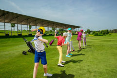 Golf school. Kids warming up at golf school at summer day Royalty Free Stock Photography