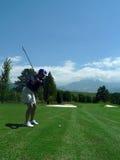 Golf-Schwingen der Frau mit szenischem Hintergrund Lizenzfreie Stockfotos
