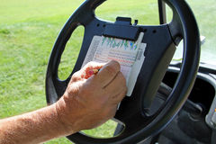 Golf Scoring. A man in a golf cart is writing down his golf score on a golf scorecard Royalty Free Stock Photos
