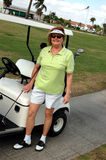 Golf senior woman. Happy senior woman and golf cart on golf course Stock Photo