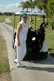 Golf senior woman. Happy senior woman choosing her club from her bag in golf cart Royalty Free Stock Photography
