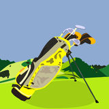 Golf set. A set of golf clubs, some in head covers, some without, in a yellow golf bag on the grass, in the mountains Royalty Free Stock Photo