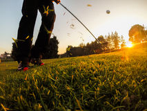 Golf: Short Game around the green. Golf: example of short game using a wedge iron club. Close-up, low angle view, sunset Stock Image