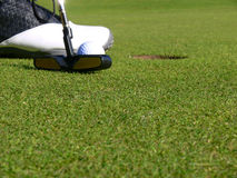 Golf - A short Putt. Close-up of a golfer concentrating to sink a short putt Stock Photography