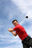 Golf Shot. Young golfer hitting an iron against a half cloudy sky Royalty Free Stock Photography