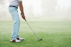 Golf shot man. Golfer hitting golf shot with club on course while on summer vacation royalty free stock photo