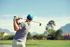 Golf shot man. Golfer hitting golf shot with club on course while on summer vacation stock images