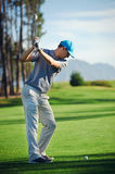 Golf shot man. Golfer hitting golf shot with club on course while on summer vacation stock photography